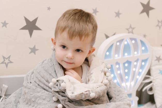 Pequeño bebé lindo que se sienta en la habitación de los niños en una casa de cama de madera con luces nocturnas en forma de globo