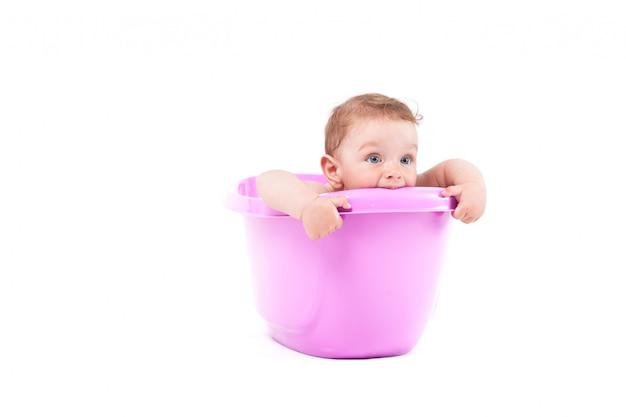 Pequeño bebé lindo tomar baño en tina púrpura