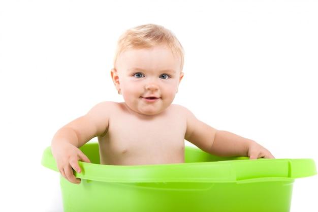 Pequeño bebé lindo tomar baño en tina verde