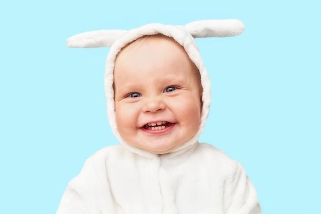 El pequeño bebé lindo en el traje del conejito está sonriendo