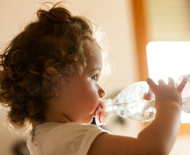 Pequeño bebé que bebe el agua dulce.