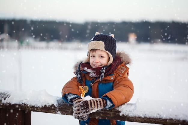 Pequeño bebé que juega y que come el gallo dulce en día de invierno. los niños juegan en el bosque nevado.