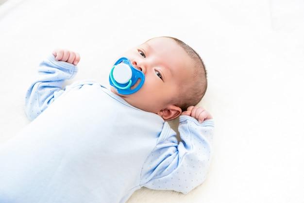 Pequeño bebé recién nacido adorable que miente en la hoja de cama blanca