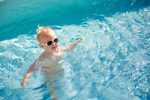 Pequeño bebé rubio lindo con las gafas de sol que salpican feliz en la piscina con agua azul clara.