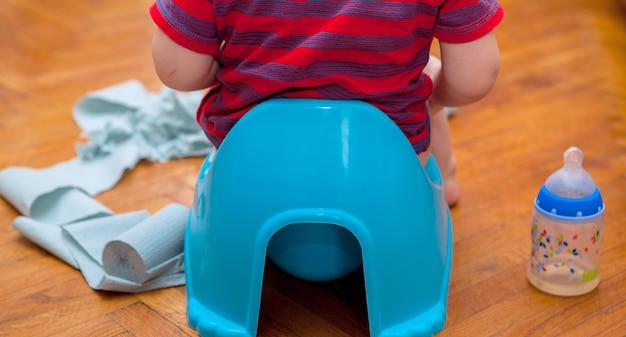 Pequeño bebé sentado en el orinal con papel higiénico y chupete sobre un fondo marrón