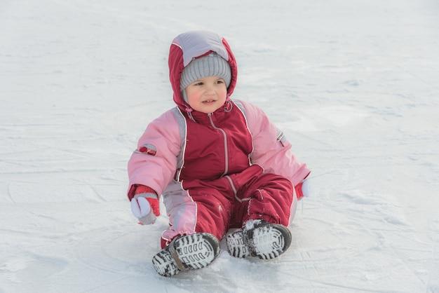 Pequeño bebé se sienta en el hielo en invierno