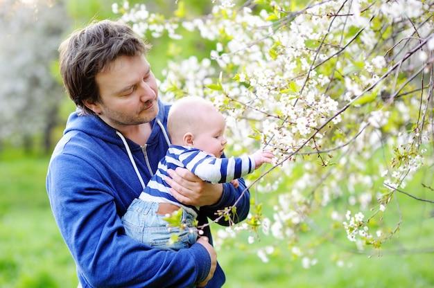 Pequeño bebé con su padre de mediana edad en el jardín de flores.