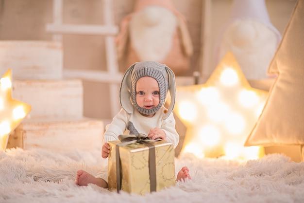 Pequeño bebé en traje de navidad como un conejo blanco jugando con la caja actual