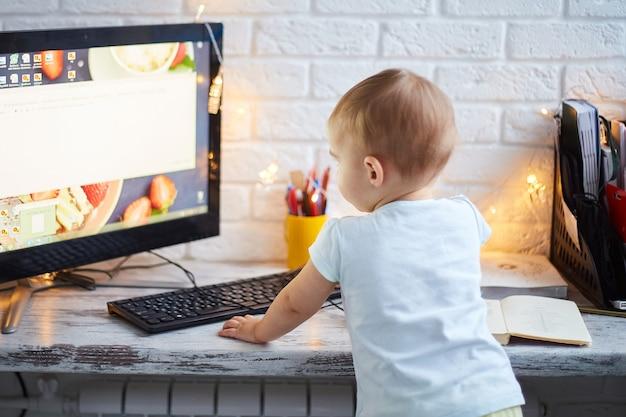 Pequeño bebé usando computadora. mamá de negocios está trabajando en el concepto de casa. lugar de trabajo decorado con luces navideñas