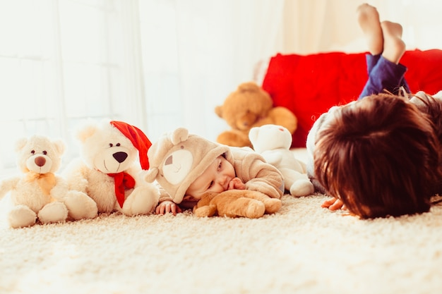 Pequeño bebé vestido como un oso se encuentra en la alfombra mullida con su m