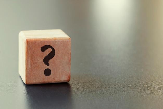 Pequeño bloque de juguete de madera con signo de interrogación