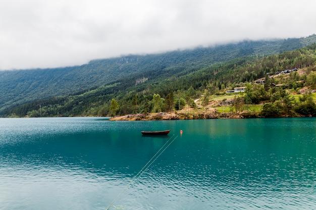 Pequeño bote amarrado en el lago azul tranquilo con montaña verde