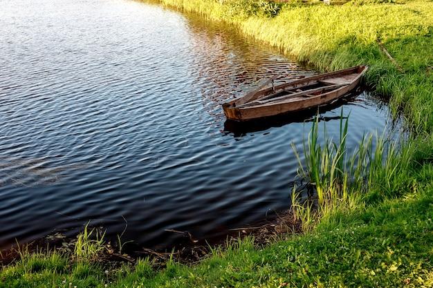 Un pequeño bote de remos de madera con un fondo roto en un lago tranquilo cerca de la orilla.