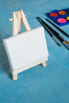 Pequeño caballete en blanco blanco de madera con pincel sobre fondo azul con textura