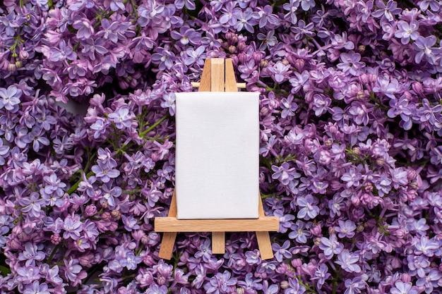 Pequeño caballete para pintar con lienzo y flores lilas.
