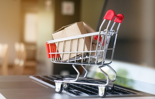 Pequeño carrito de la compra con el ordenador portátil para el concepto en línea de las compras
