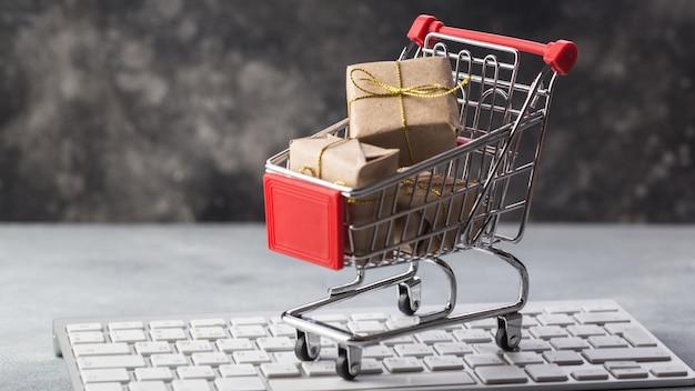 Pequeño carrito de compras con regalos y tarjeta de crédito en un teclado portátil conceptos sobre comercio en línea