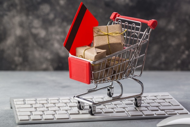 Pequeño carrito de compras con regalos y tarjeta de crédito en un teclado portátil