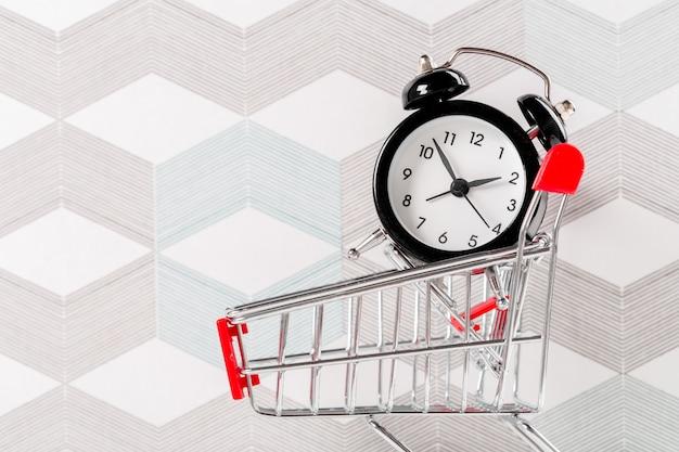 Pequeño carrito de compras con reloj despertador. concepto de tiempo de compras