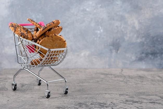 Un pequeño carrito rosa con galletas de avena saludables colocadas sobre una mesa de piedra.
