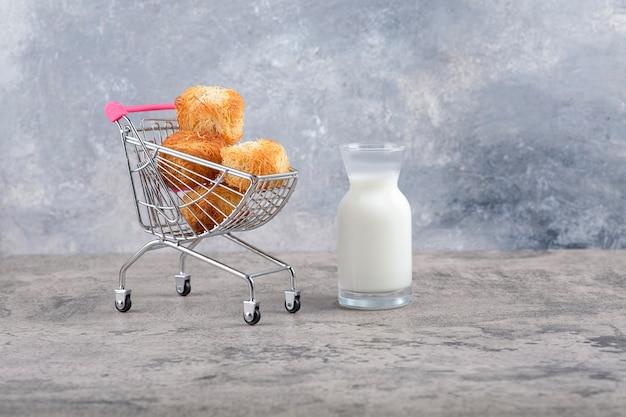 Un pequeño carrito rosa de sabrosas galletas con una jarra de vidrio de leche sobre un fondo de mármol.