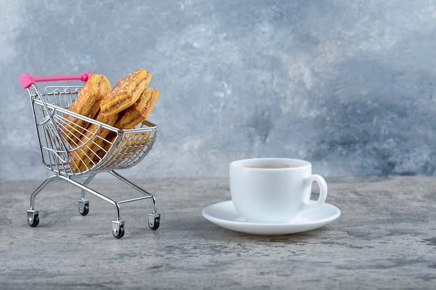 Un pequeño carrito rosa de sabrosas galletas con una taza de té caliente colocado sobre un fondo de mármol.