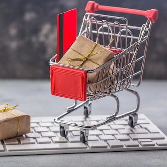 Pequeño carro de compras con regalos y tarjeta de crédito en un teclado portátil conceptos
