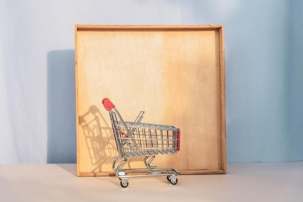 Pequeño carro de metal vacío de un supermercado que proyecta una sombra sobre el marco de madera. copie el espacio, plantilla