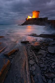 Pequeño castillo rodeado por el valiente océano atlántico en sokoa en la bahía donibane lohitzune en el país vasco.