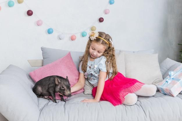 Pequeño cerdo negro y niña pequeña