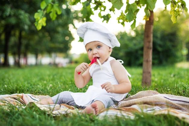 Pequeño chef cocina y come pasta en un picnic al aire libre