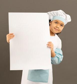 Pequeño chef lindo que sostiene la bandera vacía