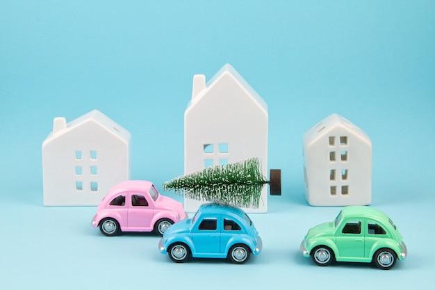 Pequeño coche de juguete carring árbol de navidad sobre el techo. vacaciones sesonal, tarjeta de felicitación