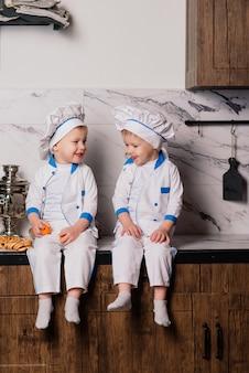 Pequeño cocinero lindo con cubiertos sentado en una cocina, hermanos gemelos, mandarina, bagels