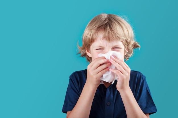 Pequeño colegial con cabello rubio estornudando a pañuelo y nariz que moquea