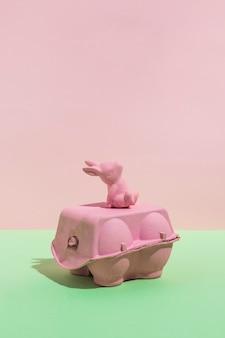 Pequeño conejo de juguete en una rejilla para huevos en la mesa