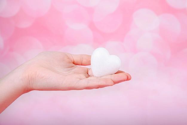 Un pequeño corazón blanco en la mano sobre fondo rosa con bohe. saludo tarjeta de san valentín