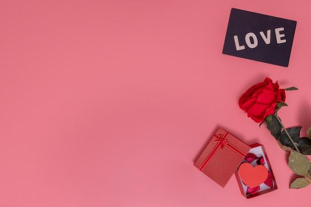 Pequeño corazón en una caja de regalo y amor palabra en una pizarra sobre un fondo rosa