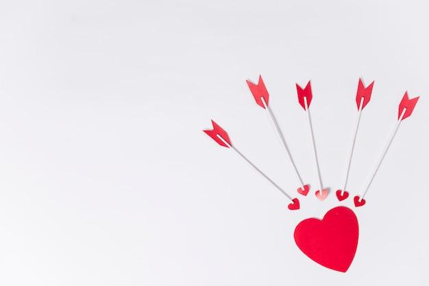Pequeño corazón con flechas de amor en la mesa