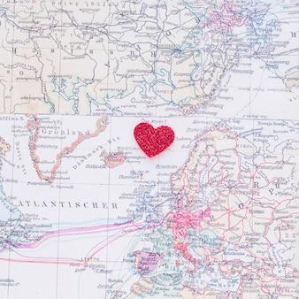 Pequeño corazón de papel rojo en el mapa del mundo