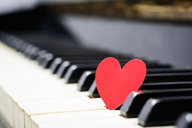 Pequeño corazón de papel rojo en las teclas del piano