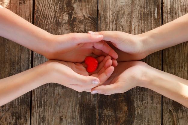 El pequeño corazón rojo está en manos de hombres y mujeres, el concepto de amor y romance.