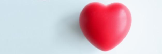 Pequeño corazón rojo sobre fondo azul borroso