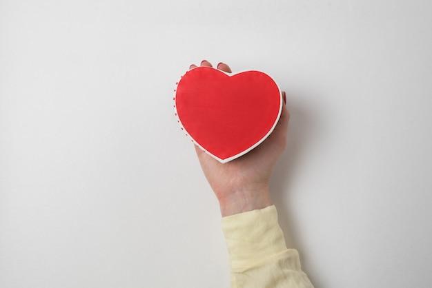 Pequeño cuadro rojo en forma de corazón en la palma femenina aislado en