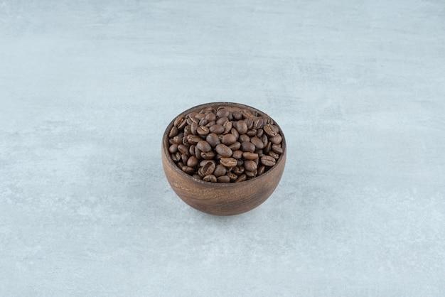 Un pequeño cuenco de madera con granos de café sobre fondo blanco. foto de alta calidad
