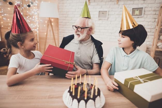 Pequeño cumpleaños fiesta niño da regalo al abuelo.
