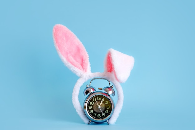 Pequeño despertador y orejas de conejo en azul pastel