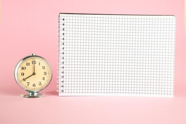 Pequeño despertador retro vintage y cuaderno sobre fondo rosa aislado