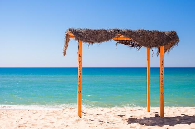 Pequeño dosel en la playa tropical vacía en la costa atlántica