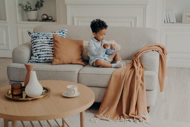 Pequeño y encantador niño afroamericano sentado en el sofá y jugando solo en la sala de estar